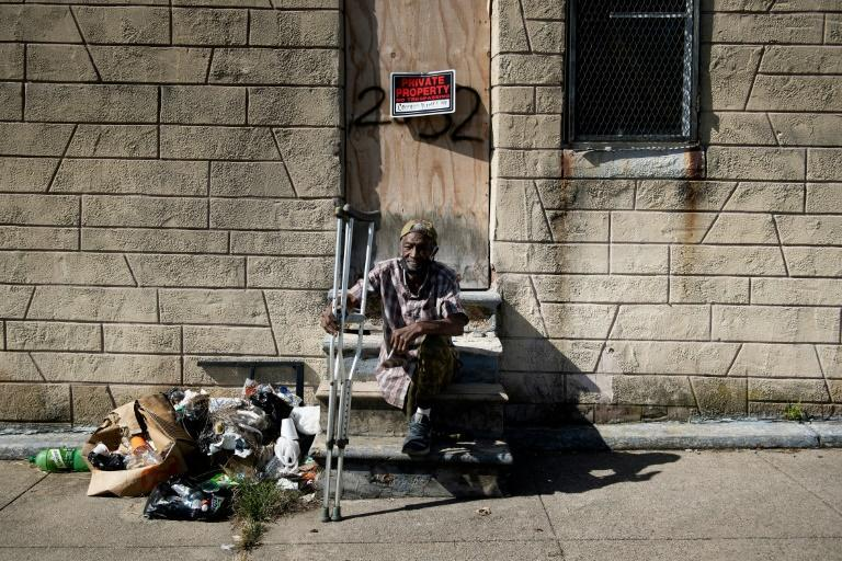 Charles Owens rests in front of an abandoned rowhouse in east Baltimore