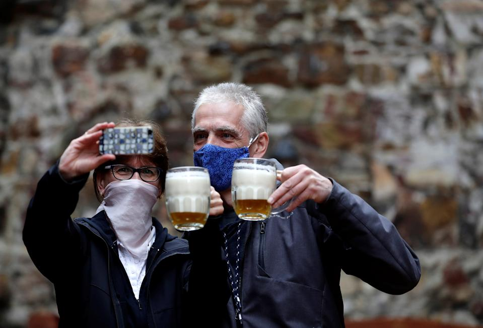 People take selfie picture with their beers at an outdoor seating of a pub in Prague