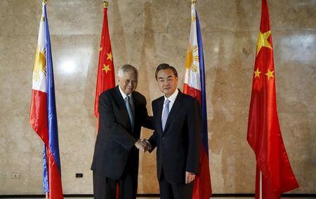 Philippine Foreign Secretary Albert del Rosario shakes hands with visiting Chinese Foreign Minister Wang Yi at the Department of Foreign Affairs in Manila