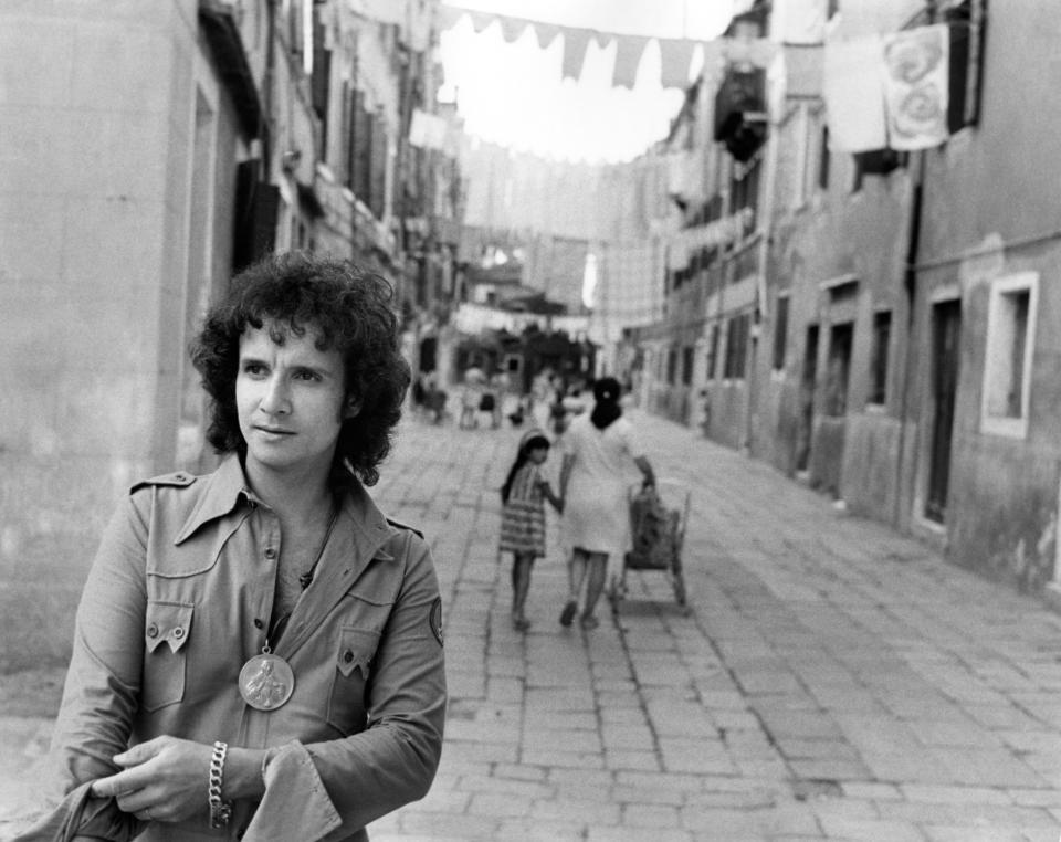 The Brasilian singer Roberto Carlos posing in a Venetian 'calla'; in the background you can see the street with hanging clothes from a window to another. Venice, Italy, 1971. (Photo by Mondadori via Getty Images)