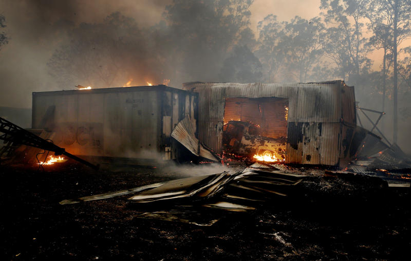 Pictured is a burning vehicle and shed on a property at Possum Brush in the Mid North Coast.
