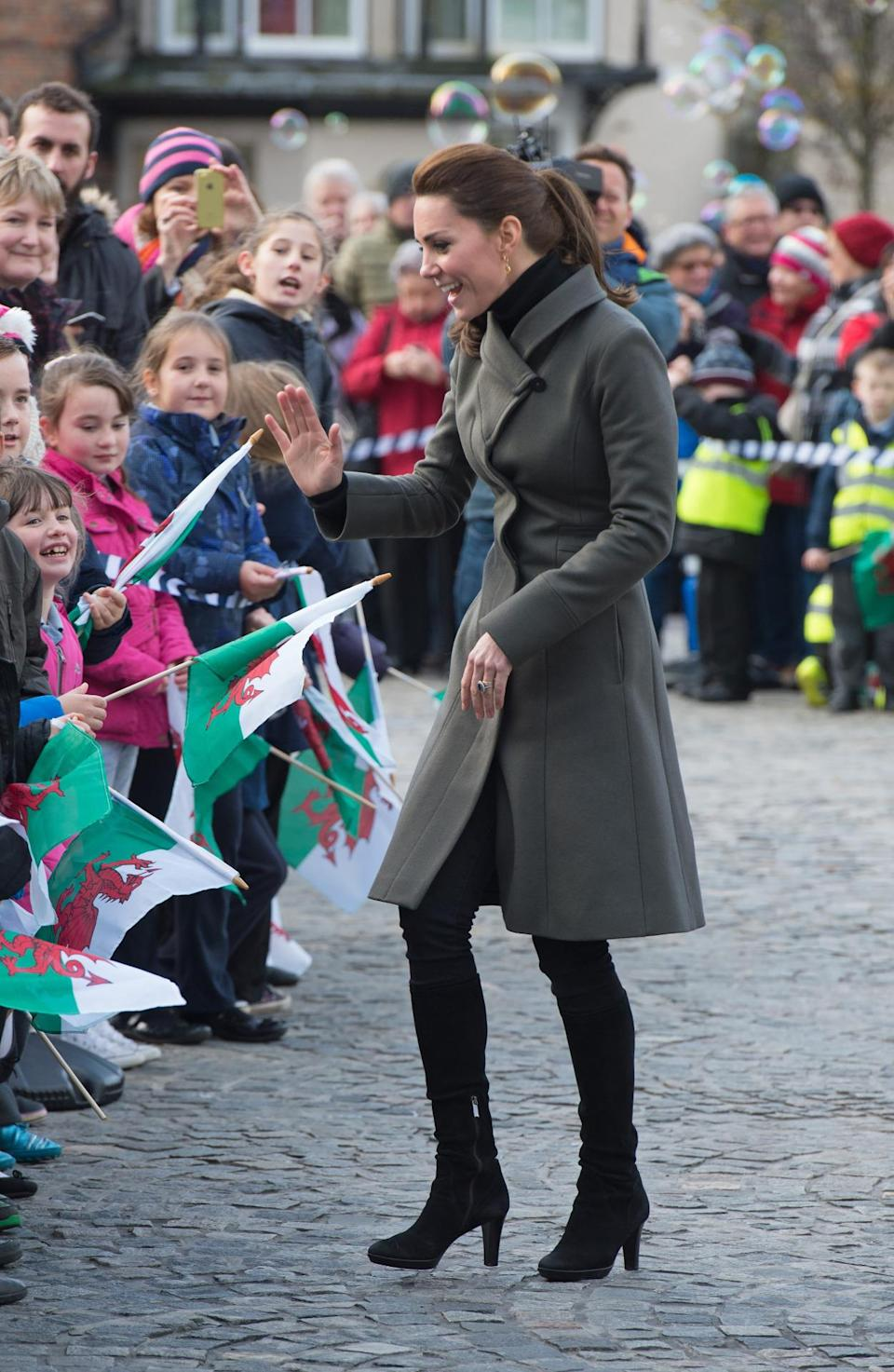 <p>For a day in Wales, Kate covered up in an olive green coat by Reiss and knee-length black boots by Italian brand, Aquatalia.</p><p><i>[Photo: PA]</i></p>