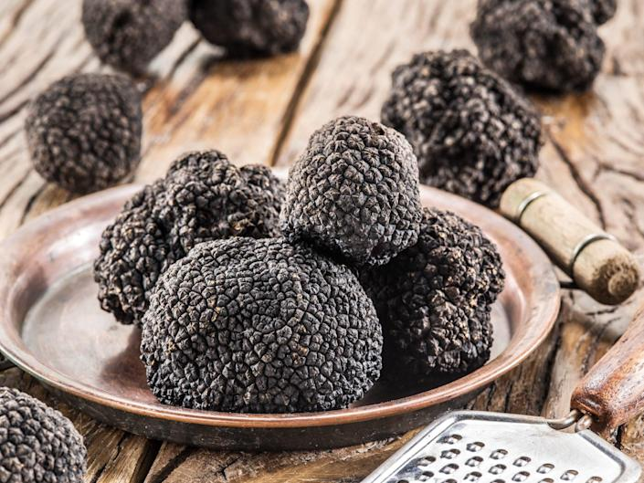 Black truffles on the plate on the old wooden table