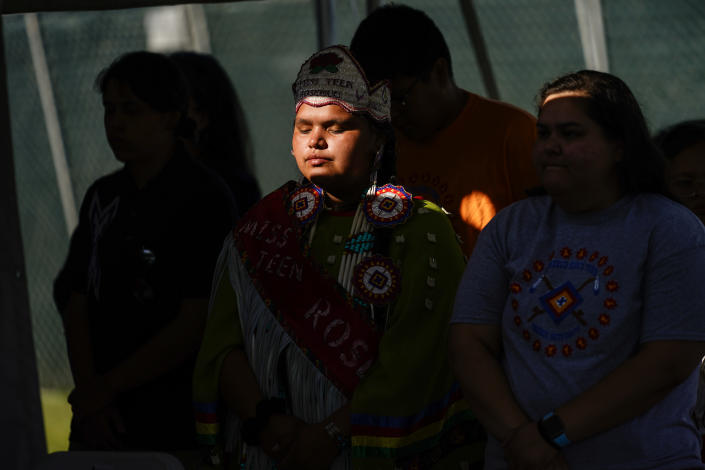 Young people from the Rosebud Sioux Tribe pray during a ceremony at the U.S. Army's Carlisle Barracks, in Carlisle, Pa., Wednesday, July 14, 2021. The disinterred remains of nine Native American children who died more than a century ago while attending a government-run school in Pennsylvania were headed home to Rosebud Sioux tribal lands in South Dakota on Wednesday after a ceremony returning them to relatives. (AP Photo/Matt Rourke)