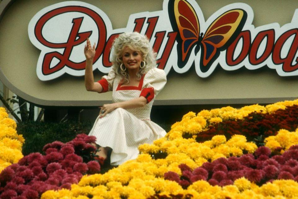 <p>Dolly waves from the sign of her theme park Dollywood, October 24, 1988 in Pigeon Forge, Tennessee. Dolly opened the park in 1986 and it's still running today!</p>
