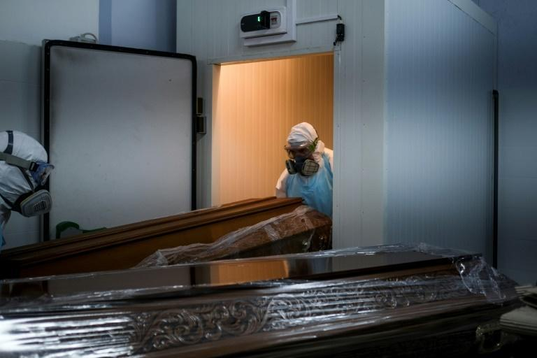 Workers place the sealed casket of a Covid victim in the crowded refrigeration room at a funeral parlour in Amadora, on the outskirts of Lisbon
