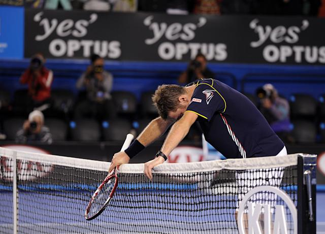 Switzerland's Stanislas Wawrinka rests on the net after losing his fourth round match against Serbia's Novak Djokovic at the Australian Open tennis championship in Melbourne, Australia, Sunday, Jan. 20, 2013. (AP Photo/Andrew Brownbill)
