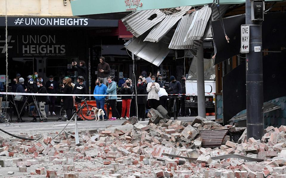 Residents gather near a damaged building in the popular shopping Chappel Street in Melbourne on Wednesday - William West /AP