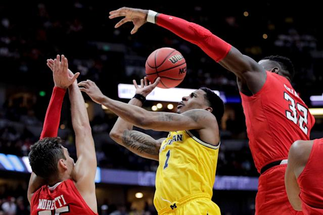 Michigan guard Charles Matthews shoots between Texas Tech guard Davide Moretti, left, center Norense Odiase during the second half an NCAA men's college basketball tournament West Region semifinal Thursday, March 28, 2019, in Anaheim, Calif. (AP Photo/Jae C. Hong)