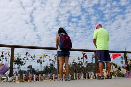 People strop to pause over a makeshift memorial near Truth Aquatics as the search continues for those missing in a pre-dawn fire that sank a commercial diving boat off a Southern California island near Santa Barbara, California