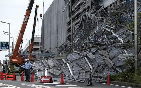 <span>Workers direct traffic in front of damaged scaffolding at the construction site of a parking garage at Haneda Airport</span> <span>Credit: Getty </span>