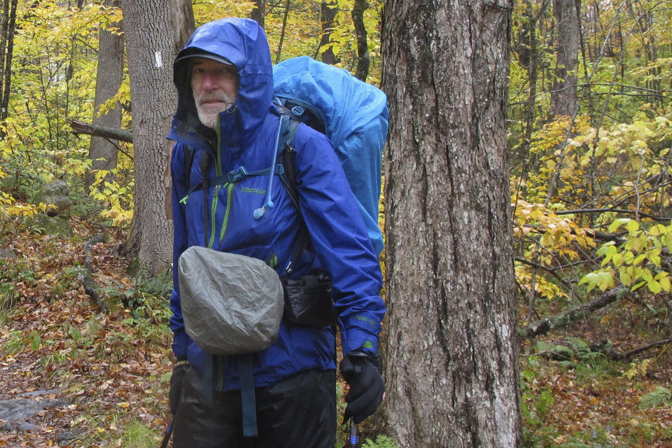 Artist Rob Mullen stands on Long Trail, the country's oldest long distance trail, in Manchester, Vt., on Tuesday, Oct. 13, 2020. Mullen was nearing the end of his 272-mile month-long hike down the length of Vermont, painting along the way. (AP Photo/Lisa Rathke)
