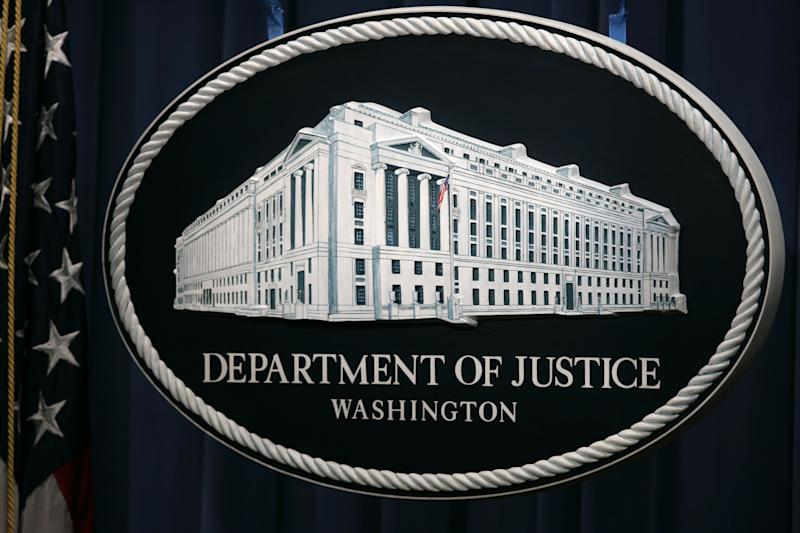 FILE- This Wednesday, Aug. 9, 2006, file photo,shows the sign that serves as the backdrop for press briefings at the Department of Justice before a press conference in Washington. The Justice Department and a number of state attorneys general on Tuesday, Aug. 13, 2013, challenged a proposed $11 billion merger between US Airways Group Inc. and American Airlines' parent company, AMR Corp. ( (AP Photo/Charles Dharapak, File)