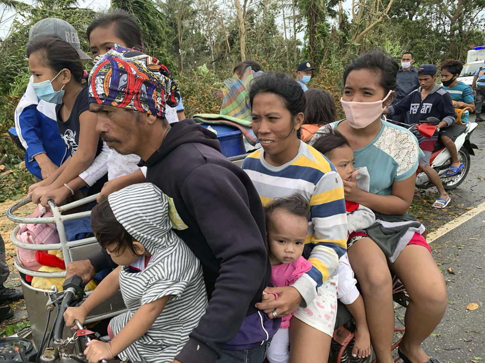 Residents evacuate to safer grounds in Pola town on the island of Mindoro, central Philippines, Monday, Oct. 26, 2020. A fast-moving typhoon forced thousands of villagers to flee to safety in provinces south of the Philippine capital Monday, flooding rural villages and ripping off roofs, officials said. (AP Photo/Erik De Castro)