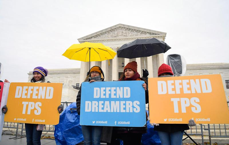 People stand in the cold and rain Tuesday before the U.S. Supreme Court hears arguments on whether the 2017 Trump administration decision to end the Deferred Action for Childhood Arrivals program (DACA) is lawful.