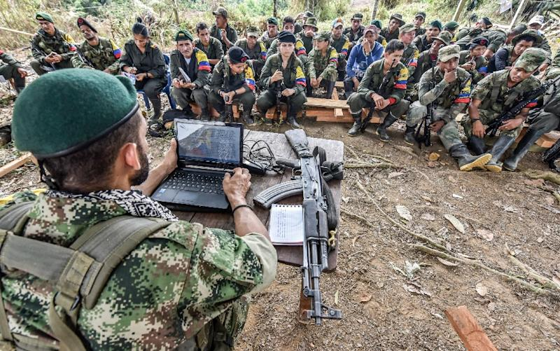 A member of the Revolutionary Armed Forces of Colombia (FARC), talks about the peace process to guerrillas during at a camp in the Colombian mountains (AFP Photo/Luis Acosta)