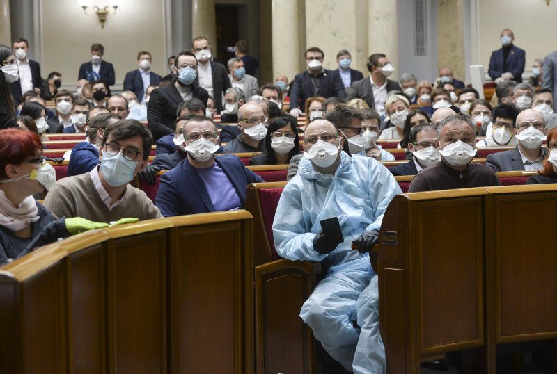Ukrainian lawmakers wearing face masks to protect against coronavirus attend an extraordinary parliamentary session in Kyiv, Ukraine, Monday, March 30, 2020. Ukraine has been under quarantine since March 12. The new coronavirus causes mild or moderate symptoms for most people, but for some, especially older adults and people with existing health problems, it can cause more severe illness or death. (AP Photo)