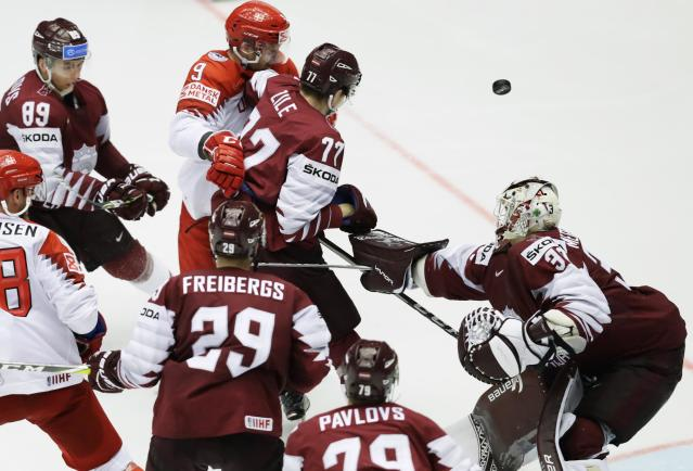 Ice Hockey - 2018 IIHF World Championships - Group B - Latvia v Denmark - Jyske Bank Boxen - Herning, Denmark - May 15, 2018 - Fredrik Storm of Denmark in action with Kristaps Zile and goaltender Elvis Merzlikins of Latvia. REUTERS/David W Cerny