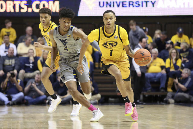 Missouri guard Xavier Pinson (1) drives it up court as he is defended by West Virginia guard Miles McBride (4) and Missouri forward Tray Jackson, behind, looks on during the first half of an NCAA college basketball game Saturday, Jan. 25, 2020, in Morgantown, W.Va. (AP Photo/Kathleen Batten)