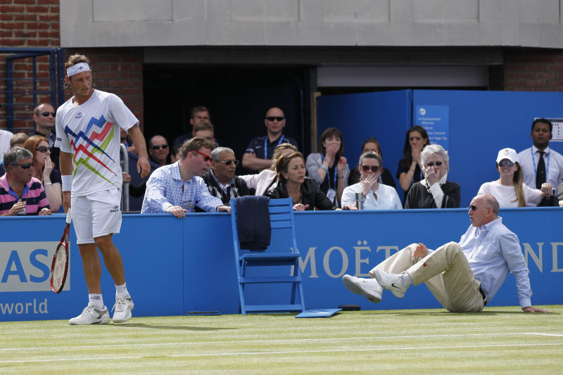 Argentina's David Nalbandian, left, looks on after causing an injury to the line judge, right, and is disqualified during the Queen's Club grass court championships final tennis match against Croatia's Marin Cilic, London, Sunday, June 17, 2012. Nalbandian kicked the small barrier surrounding the line judge in anger. A piece of the barrier then hit the line judge, causing bleeding on his left shin. (AP Photo/Sang Tan)