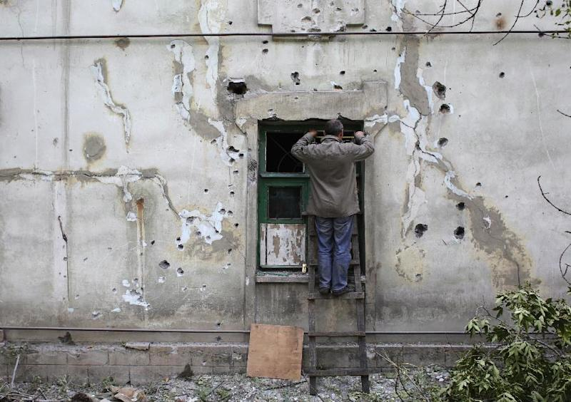 A man covers a broken window in Debaltseve, after his building was damaged by rockets during an overnight shelling on September 22, 2014 (AFP Photo/Anatolii Stepanov)