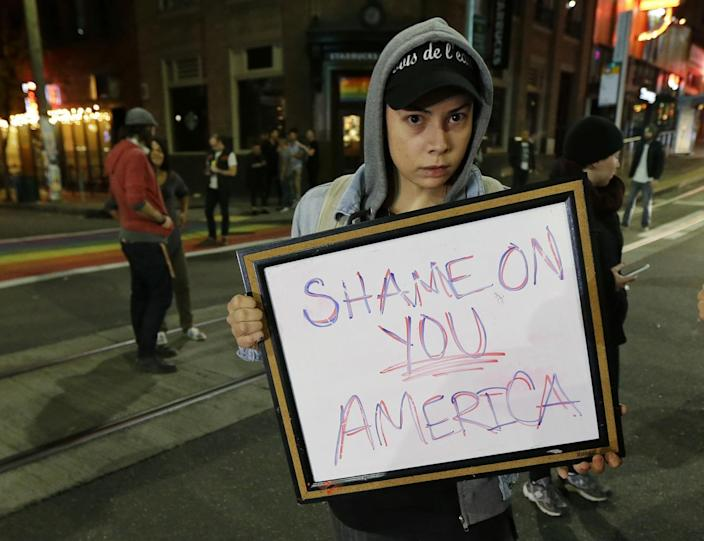 """<p>Felomina Cervantes, of Seattle, holds a sign that reads """"Shame on You America"""" as she takes part in a protest against President-elect Donald Trump, Wednesday, Nov. 9, 2016, in Seattle's Capitol Hill neighborhood. (Photo: Ted S. Warren/AP) </p>"""