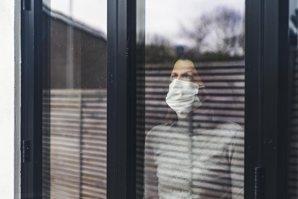 Woman with mask looking out of window