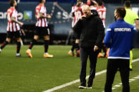 Real Madrid's head coach Zinedine Zidane gestures as Athletic Bilbao players, background, celebrate their first goal during Spanish Super Cup semi final soccer match between Real Madrid and Athletic Bilbao at La Rosaleda stadium in Malaga, Spain, Thursday, Jan. 14, 2021. (AP Photo/Jose Breton)