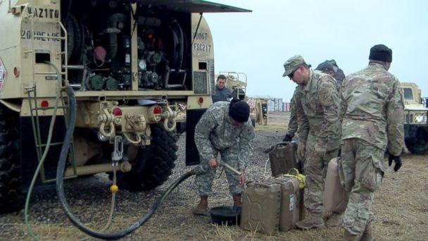 PHOTO: U.S. Army soldiers fuel up gas tanks. (Quinn Owen/ABC News)