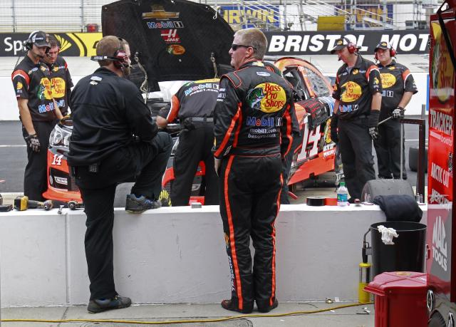 Driver Jeff Burton (14) stands behind the wall as his crew works on his car during practice for the Irwin Tools Night Race NASCAR Sprint Cup Series auto race at Bristol Motor Speedway on Friday, Aug. 22, 2014, in Bristol, Tenn. (AP Photo/Wade Payne)