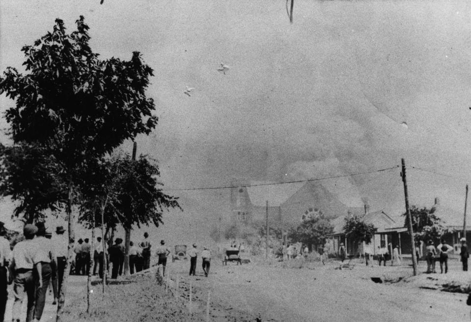 This photo provided by the Department of Special Collections, McFarlin Library, The University of Tulsa shows a crowd watching the Mt. Zion Baptist Church burn during the June 1, 1921, Tulsa Race Massacre in Tulsa, Okla. (Department of Special Collections, McFarlin Library, The University of Tulsa via AP)