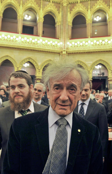 """FILE - In this Dec. 9, 2009, file photo, Elie Wiesel, Holocaust survivor and Nobel Peace Prize winning author, center, stands in the Hungarian Parliament building in Budapest during his first official visit to the country since the Holocaust. Wiesel says he's """"repudiating"""" a Hungarian government award he received in 2004 because top officials in Budapest attended a ceremony for a Nazi sympathizer. (AP Photo/Bela Szandelszky, File)"""