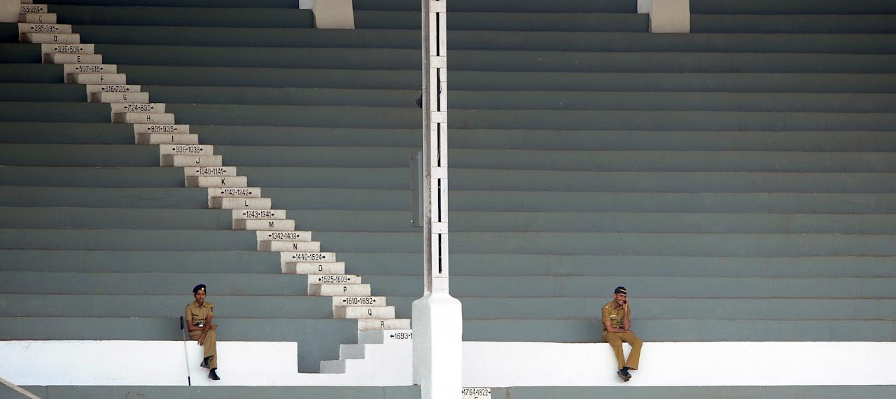 Indian policemen sit in the empty stands during the inugural match of the ICC Women's World Cup 2013 between India and West Indies at the Cricket Club of India's Brabourne stadium in Mumbai on January 31, 2013. Teams from Australia, England, New Zealand, Pakistan, South Africa, Sri Lanka, West Indies join hosts India for the global event which is being played from 31 January to 17 February.  The women's World Cup opened in Mumbai with the cricketers hoping to put aside memories of the unsavoury build-up and gain their due recognition in a country where the men's game reigns supreme. AFP PHOTO/ Indranil MUKHERJEE        (Photo credit should read INDRANIL MUKHERJEE/AFP/Getty Images)