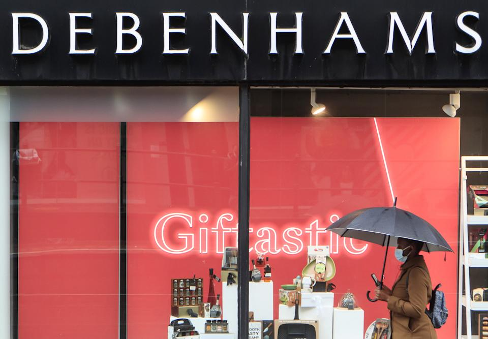 A woman walks past a Debenhams store in Manchester in the final week of a four week national lockdown to curb the spread of coronavirus. (Photo by Danny Lawson/PA Images via Getty Images)