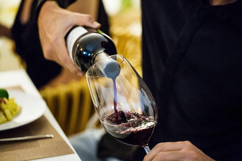 man pouring red wine in glass