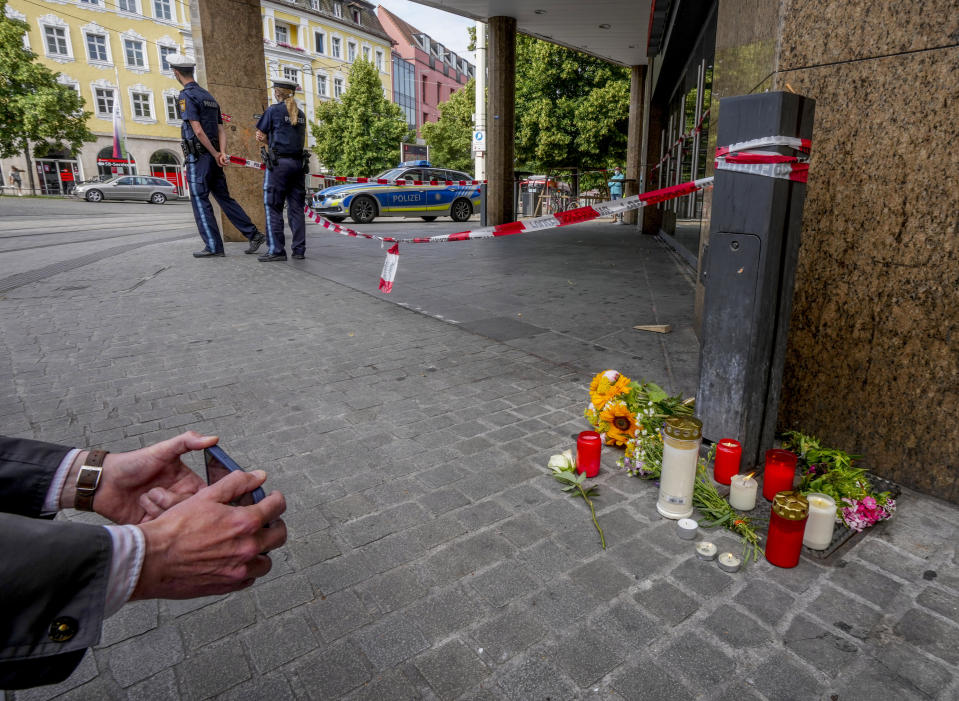 Flowers and candles were laid at the crime scene in central Wuerzburg, Germany, Saturday, June 26, 2021. German police say several people have been killed and others injured in a knife attack in the southern city of Wuerzburg on Friday.(AP Photo/Michael Probst)