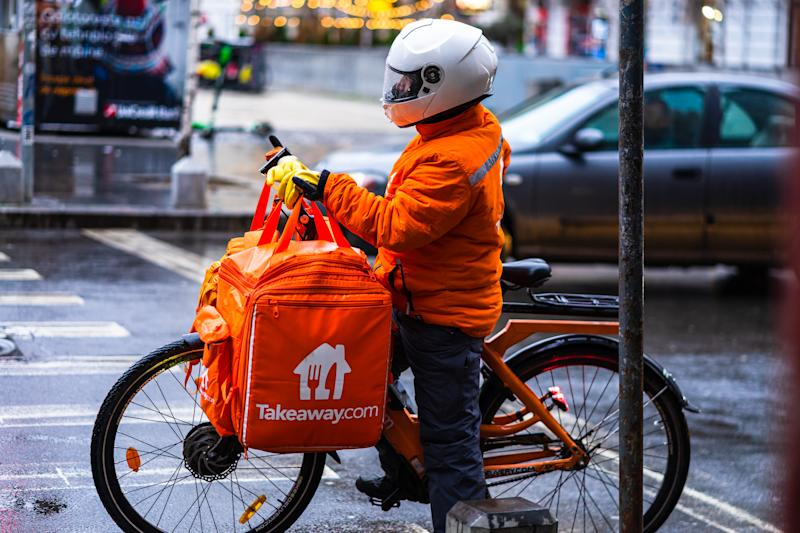 Young man on an electric bike with takeaway.com logo delivering food during a rainy day in Bucharest, Romania, 2020