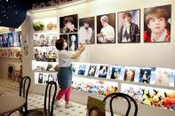 Cafe owner Kim Eun-hee, fan of K-pop boy band BTS, wipes the dust off the picture frame in her cafe in Seoul