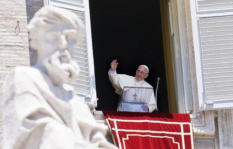 Pope Francis waves during his Sunday Angelus from the window of his study overlooking St.Peter's Square at the Vatican on July 6, 2014 (AFP Photo/Filippo Monteforte)