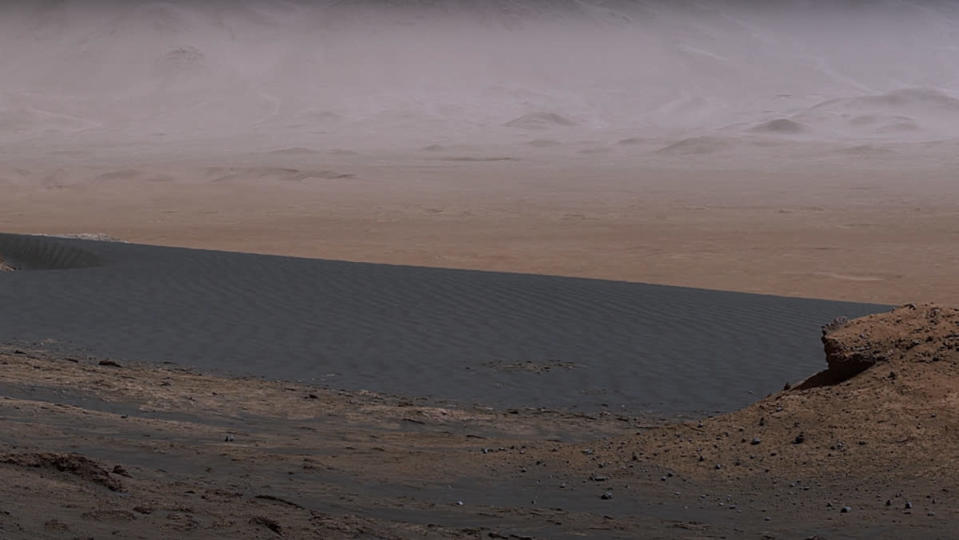 A stretch of dark gray sand dunes on the reddish rocky surface of Mars.