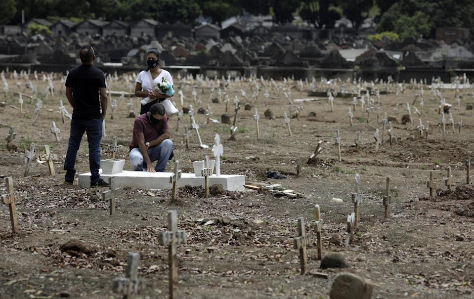 A group reacts next to a grave during the celebration of the Day of the Dead, amid the coronavirus disease (COVID-19) pandemic, at Sao Francisco Xavier cemetery in Rio de Janeiro, Brazil, November 2, 2020. REUTERS/Ricardo Moraes