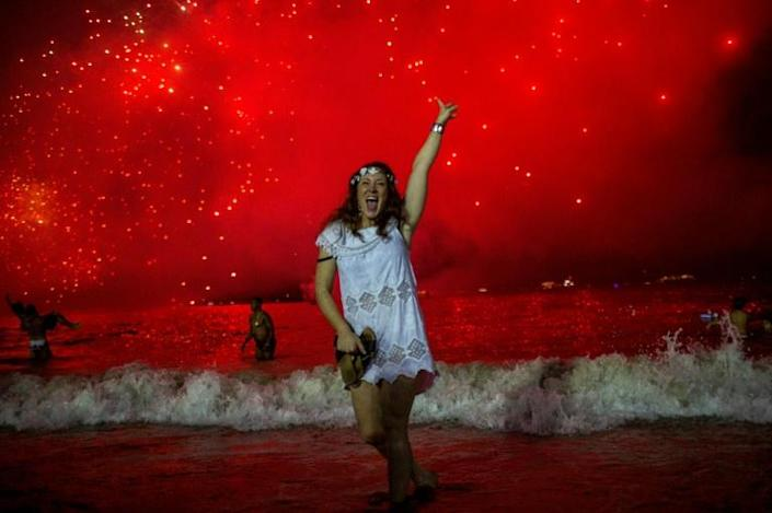 A woman celebrates at the traditional New Year's fireworks show at Copacabana Beach in Rio de Janeiro, Brazil in 2019. With not so many people following restrictions and authorities' orders and counter-orders to limit crowds during the end of the year holidays, Brazilians will have a difficult time avoiding a brutal worsening of the coronavirus pandemic, analysts warn