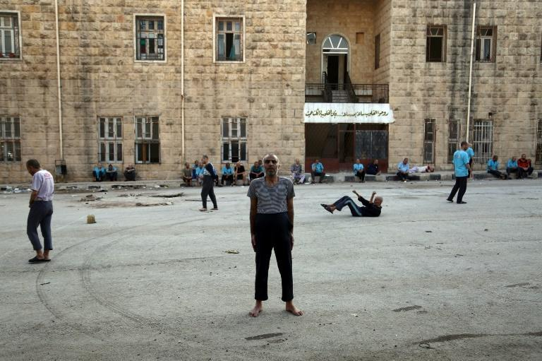 Syrian patients in the yard of a mental health clinic, the sole such facility in Syria's rebel-held north, on July 6, 2017