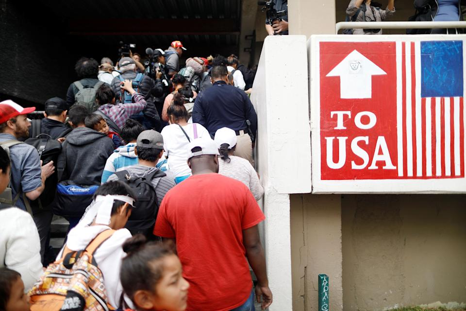 Caravan members pass by signs marking the way to the United States border.