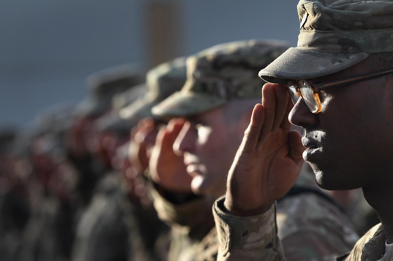 BAGRAM, AFGHANISTAN - SEPTEMBER 11:  U.S. Army soldiers salute during the national anthem during the an anniversary ceremony of the terrorist attacks on September 11, 2001 on September 11, 2011 at Bagram Air Field, Afghanistan. Ten years after the 9/11 attacks in the United States and after almost a decade war in Afghanistan, American soldiers paid their respects in a solemn observence of the tragic day.  (Photo by John Moore/Getty Images)