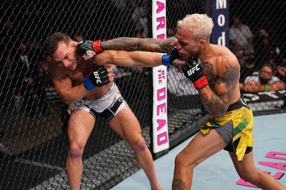 HOUSTON, TEXAS - MAY 15: (R-L) Charles Oliveira of Brazil punches Michael Chandler in their UFC lightweight championship bout at Toyota Center on May 15, 2021 in Houston, Texas. (Photo by Josh Hedges/Zuffa LLC)