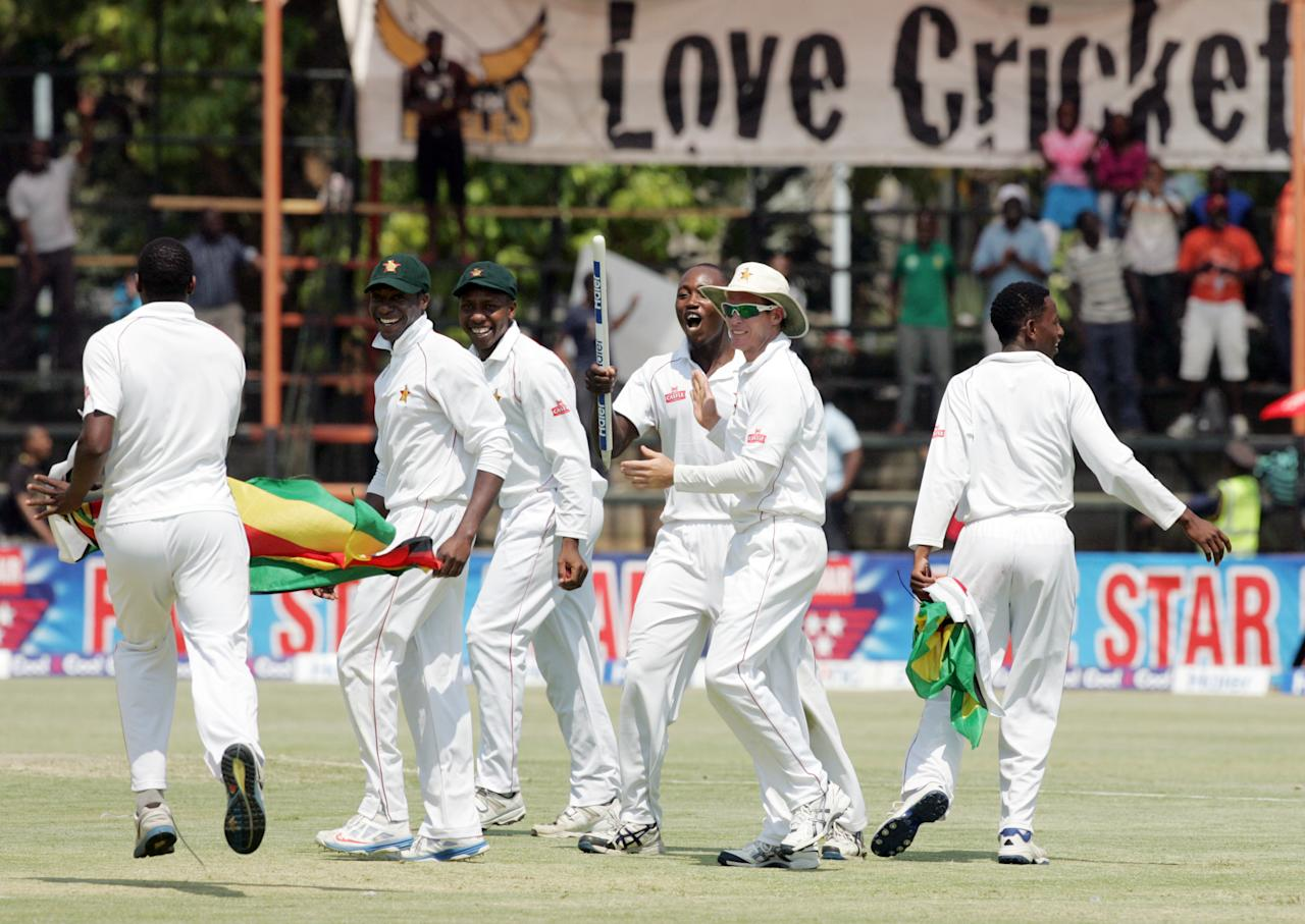 Zimbabwe players celebrate victory over Pakistan on September 14, 2013 during the fifth day of the second Test against at the Harare Sports Club.                              AFP PHOTO / JEKESAI NJIKIZANA        (Photo credit should read JEKESAI NJIKIZANA/AFP/Getty Images)