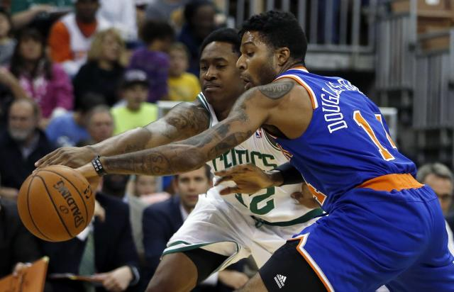 Boston Celtics' MarShon Brooks (12) battles for the ball with New York Knicks' Chris Douglas-Roberts (14) in the second quarter of an NBA preseason basketball game in Manchester, N.H., Saturday, Oct. 12, 2013. (AP Photo/Michael Dwyer)