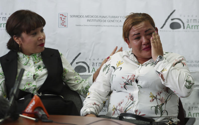 Jenifer De La Rosa, left, comforts her sister Angela Rendon, right, during a press conference in Bogota, Colombia, Thursday, Nov. 14, 2019. The story of the lost sisters could be one of many involving children who were separated from their parents after the Nevado del Ruiz erupted, rescued from the rubble and later put up for adoption after no relative arrived to claim them . A genetic institute in Colombia's capital confirmed through DNA testing that Jenifer De La Rosa and Angela Rendon are sisters. (AP Photo/Fernando Vergara)