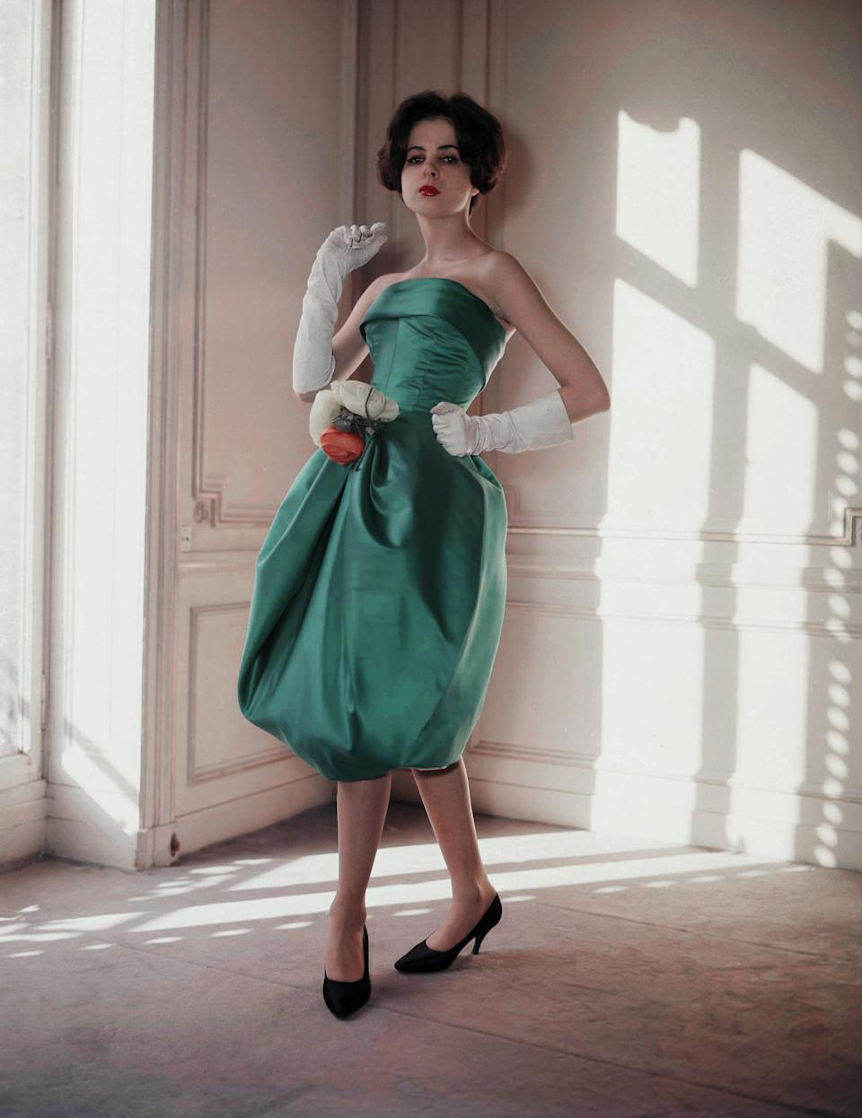 "A ""bubble dress"" by Pierre Cardin in his 1958 spring-summer collection is a short evening dress in turquoise blue satin trimmed with a bouquet of yellow roses at the waist."